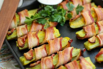Bacon wrapped pickles on the cast iron baking pan garnished with fresh parsley and ranch dip.