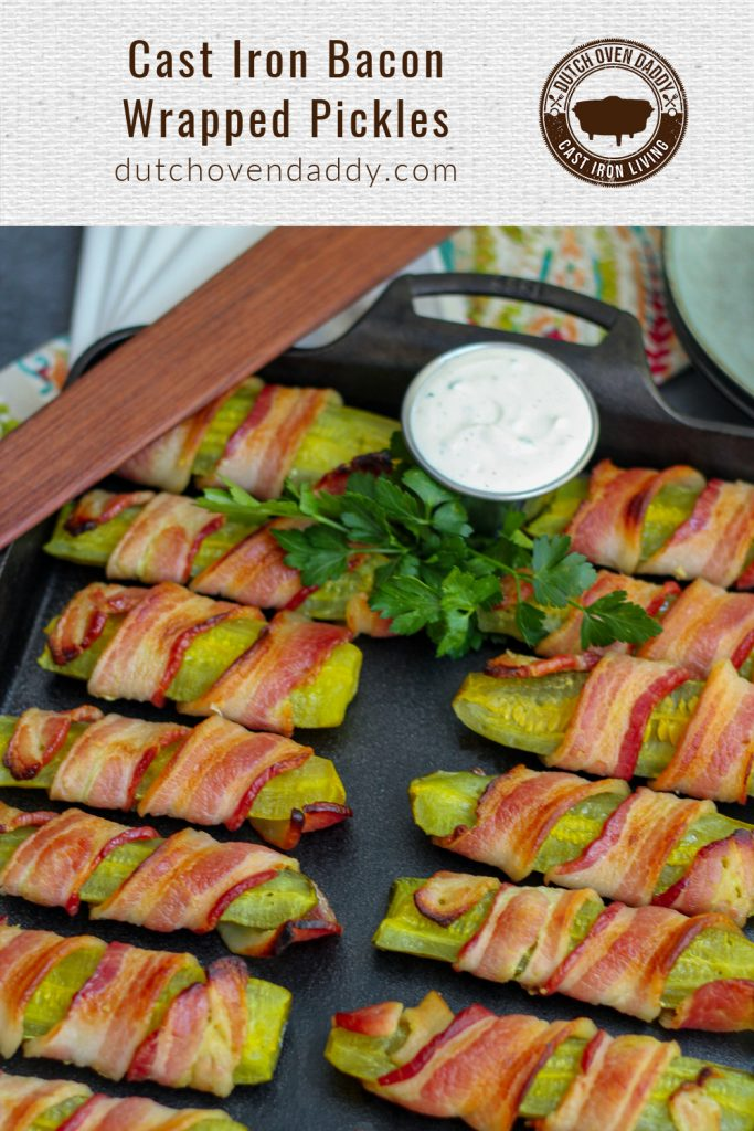 Branded image of bacon wrapped pickles on a cast iron baking pan garnished with fresh parsley and ranch dipping sauce.
