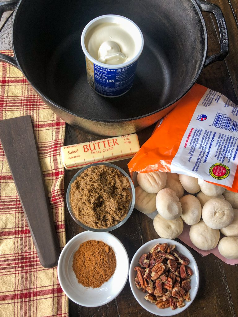Ingredients to make the recipe: cinnamon, pecans, frozen dinner rolls, brown sugar, butter, prepared cream cheese frosting, and the Dutch oven.