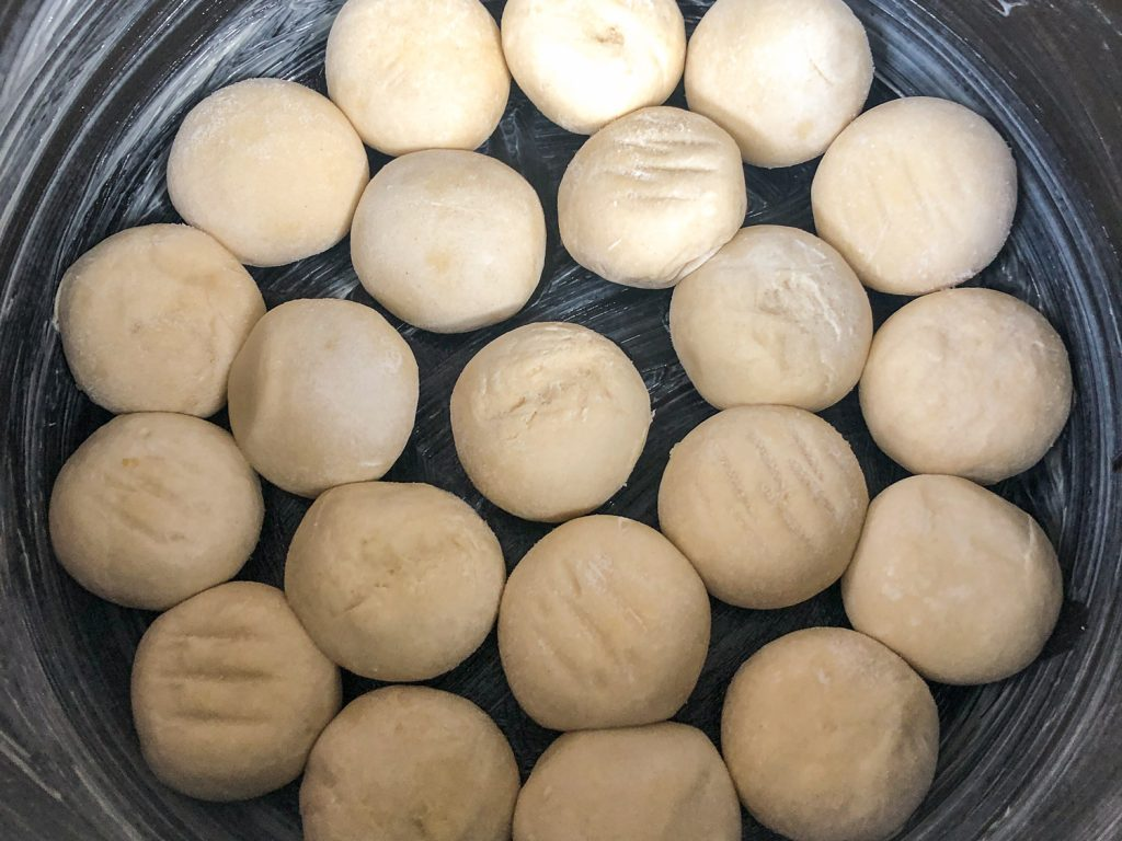 Frozen dough balls arranged in the coated pot to rise.
