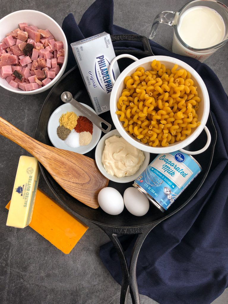 Ingredients to make Skillet Ham Macaroni and Cheese: milk, ham, cream cheese, noodles, evaporated milk, mayonnaise, eggs, butter, cheese, seasonings and spices.