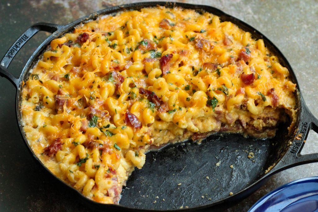 Cooked Skillet Ham Macaroni and Cheese with a portion missing.