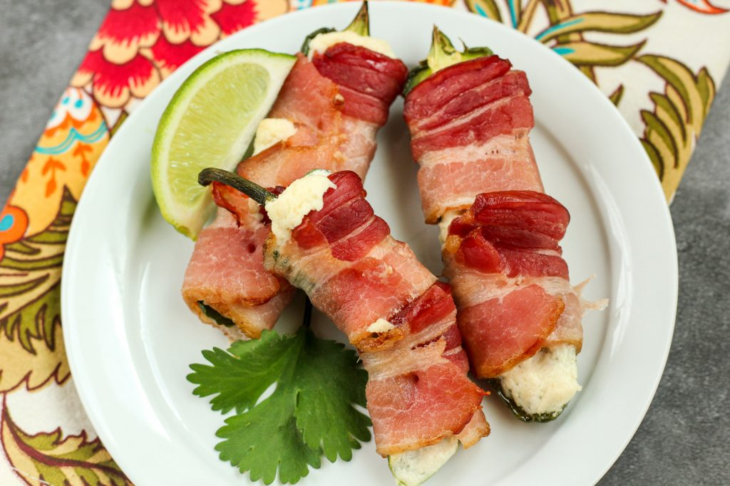 A white plate of 3 bacon wrapped jalapeño poppers with a lime wedge.