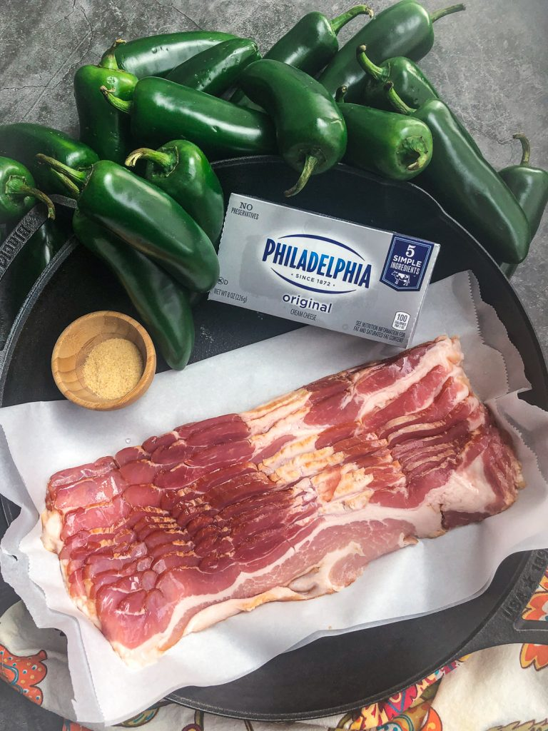 Ingredients to make the recipe: fresh whole jalapeños, cream cheese, bacon, and granulated garlic in a cast iron skillet.