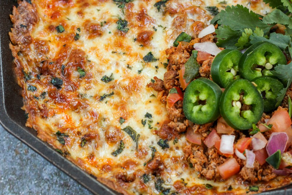 Close up image of the garnished chorizo and cheese dip still in the cast iron skillet.