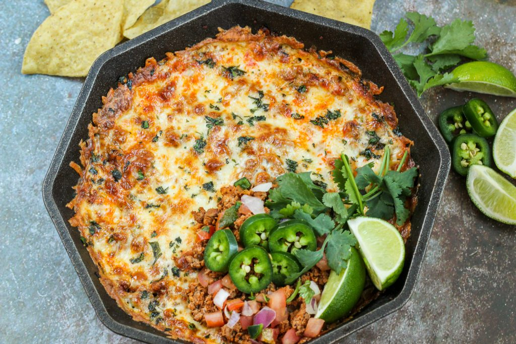 Cooked and garnished skillet chorizo cheese dip.