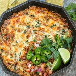 Skillet chorizo cheese dip garnished with chips in the background.